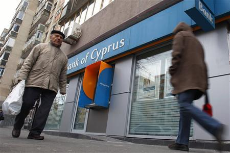 People walk past a branch of Bank of Cyprus in Bucharest March 25, 2013. REUTERS/Bogdan Cristel