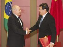 Министр финансов Бразилии Гидо Монтега (слева) и его китайский коллега Лоу Цзивэй обмениваются рукопожатием после подписания меморандума о пониманиии на саммите БРИКС в Дурбане 26 марта 2013 года. Китай и Бразилия, члены блока БРИКС, во вторник договорились о торговле в своих собственных валютах на сумму до $30 миллиардов в год, выведя таким образом почти половину своего торгового обмена из долларовой зоны. REUTERS/Rogan Ward