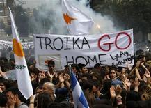 Devant le palais présidentiel à Nicosie, mardi. Plusieurs milliers de personnes ont manifesté mardi dans les rues de la capitale chypriote au lendemain d'un plan de sauvetage qui s'annonce douloureux. Le président de Bank of Cyprus, première banque de l'île, a remis sa démission et les banques sont restées fermées pour le 11e jour consécutif. /Photo prise le 26 mars 2013/REUTERS/Yannis Behrakis