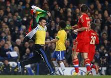 Homem corre no campo com uma bandeira durante amistoso entre Brasil e Rússia em Stamford Bridge, em Londres. 25/03/2013 REUTERS/Andrew Winning