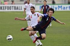 Jogador do Japão Shinji Okazaki enfrenta Basem Othman da Jordânia, durante partida de futebol classificatória para a Copa do Mundo de 2014, no estádio King Abdullah, em Amman, capital da Jordânia. 25 de março de 2013. O Japão desperdiçou um pênalti no segundo tempo e perdeu a oportunidade de se tornar o primeiro time a se classificar para a Copa do Mundo de 2014, ao ser surpreendentemente derrotado por 2 x 1 pela Jordânia em um jogo tenso 25/03/2013 REUTERS/Muhammad Hamed