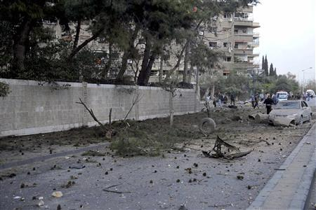Debris and damaged vehicles are pictured on a street after a car bomb exploded in Damascus March 26, 2013, in this handout photograph distributed by Syria's national news agency SANA. REUTERS/SANA/Handout