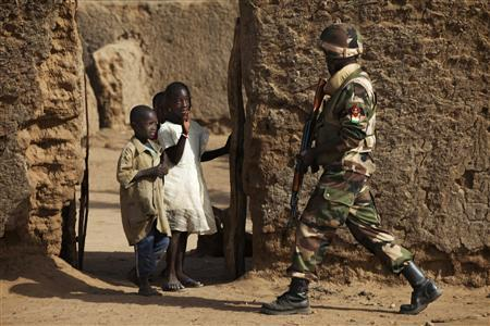 Children wave at a soldier from Niger on patrol in Gao, February 27, 2013. Niger has sent troops to Mali as part of the MISMA West African forces. REUTERS/Joe Penney