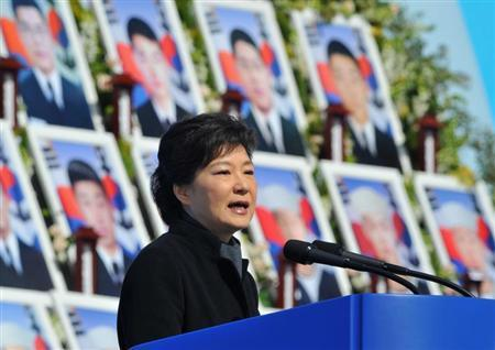 South Korea's President Park Geun-Hye speaks in front of photographs of sailors who died, during an event marking the third anniversary of the sinking of a South Korean naval vessel by what Seoul insists was a North Korean submarine, at the national cemetery in Daejeon March 26, 2013. REUTERS/Kim Jae-Hwan/Pool
