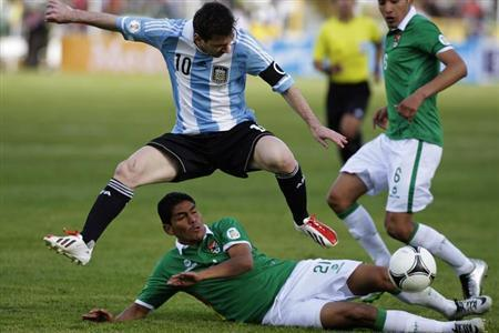 Argentina's Lionel Messi (top) jumps over Bolivia's Edward Zenteno during their 2014 World Cup qualifying soccer match in La Paz March 26, 2013. REUTERS/Gaston Brito