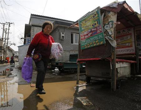 A woman walks past a poster for a medical ointment at a street market on the outskirts of Beijing March 20, 2013. REUTERS/Kim Kyung-Hoon