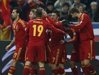 Игроки сборной Испании празднуют гол в ворота французов в отборочном матче к ЧМ-2014 в Париже 26 марта 2013 года. Сильнейшие национальные сборные Европы набрали во вторник по три очка в отборочных матчах к чемпионату мира в Бразилии, и лишь английская команда не смогла добиться победы. REUTERS/Benoit Tessier