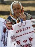 Женщина продает национальные одежды и платки в центре Киева 23 июля 2012 года. Относительно благополучное разрешение банковского кризиса на Кипре подогреет спрос на риск, чем облегчит запланированное возвращение Украины на внешний долговой рынок во втором квартале и поможет Киеву на открывающихся в среду переговорах с МВФ, который требует болезненных реформ в обмен на кредиты. REUTERS/Gleb Garanich