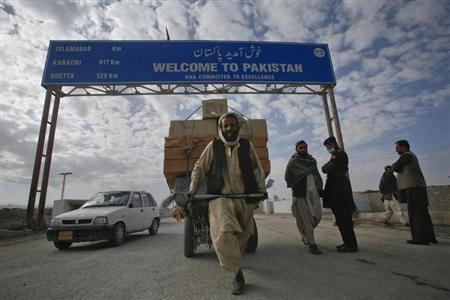 A Pashtun man passes a road sign while pulling supplies towards the Pakistan-Afghanistan border crossing in Chaman November 28, 2011.REUTERS/Naseer Ahmed/Files