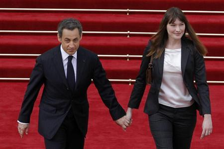 Nicolas Sarkozy (L) and Carla Bruni-Sarkozy leave the Elysee Palace at the end of a handover ceremony in Paris May 15, 2012. REUTERS/Patrick Kovarik/Pool