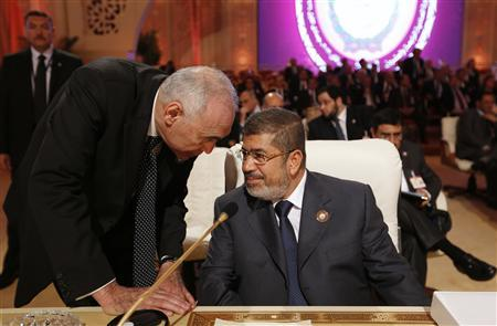 Egypt's President Mohamed Mursi (R) speaks to Egypt's Foreign Minister Mohamed Kamel Amr during the opening of the Arab League summit in Doha March 26, 2013. REUTERS/Ahmed Jadallah