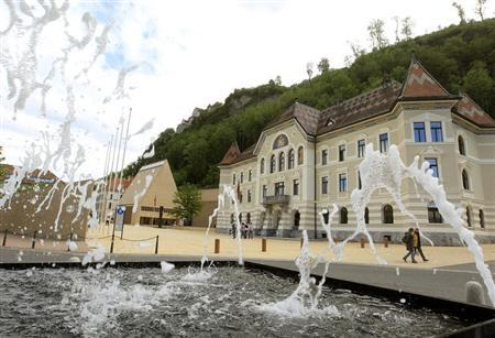 People walk past the government building (R) and the Landtag parliament (back L) in Liechtenstein's capital Vaduz May 21, 2012. REUTERS/Arnd Wiegmann