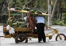 A man arranges vegetables for sale on a tricycle in the village of Sagua La Grande in central Cuba, around 240 km (149 miles) east of Havana March 10, 2013. REUTERS/Desmond Boylan