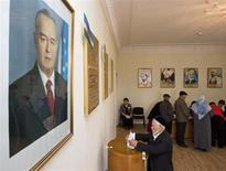 Избиратель опускает бюллетен в урну под портретом президента Узбекистана Ислама Каримова на участке для голосования в Ташкенте. REUTERS/Shamil Zhumatov