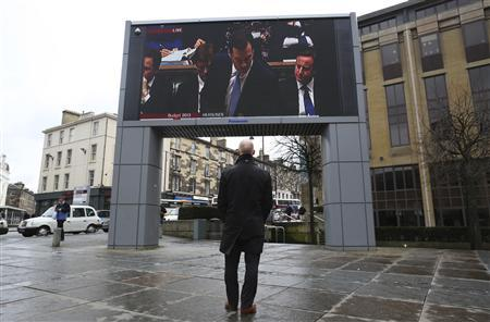A man watches a screen showing Chancellor George Osborne delivering his budget, Edinburgh in Scotland March 20, 2013. REUTERS/David Moir