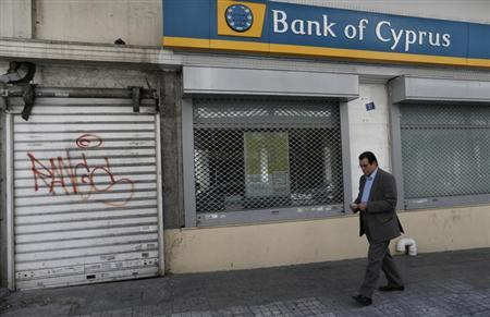 A man walks outside a closed Bank of Cyprus branch in Athens March 26, 2013. Greece's Piraeus Bank said on Tuesday it agreed to buy the branches of all three Cypriot banks in Greece for 524 million euros ($675.04 million) in cash. REUTERS/John Kolesidis