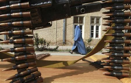 An Afghan woman walks inside a police compound as former Afghan Taliban members hand over their weapons after joining the Afghan government's reconciliation and reintegration programme in Herat province March 19, 2013. REUTERS/Mohmmad Shoib