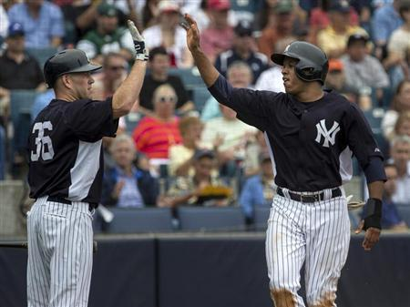New York Yankees' Thomas Neal (R) celebrates with teammate Kevin Youkilis after scoring against the Boston Red Sox during the second inning of their MLB spring training baseball game in Tampa, Florida March 20, 2013. REUTERS/Scott Audette
