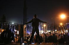 A protester stands atop the fence at the Presidential Palace during an anti-bailout rally in Nicosia March 27, 2013. REUTERS/Yannis Behrakis