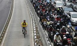 A man rides a bicycle in a bus lane next to a morning rush hour traffic jam in Jakarta in this November 10, 2011 file photo. Indonesia is seeking European investors for $9 billion worth of water, road, air and seaport projects in what will be a litmus test of Southeast Asian countries' ability to seize on ripe financial conditions to upgrade decrepit infrastructure. Picture taken November 10, 2011. To match Analysis SOUTHEASTASIA-INFRASTRUCTURE/ REUTERS/Supri/Files