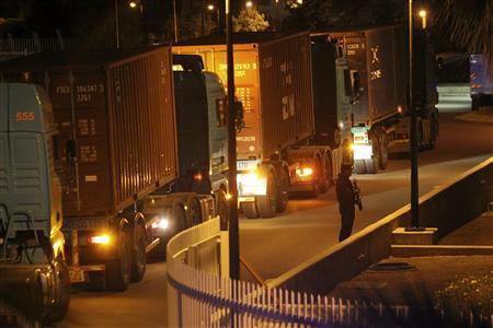 A policeman stands guard in front of trucks carrying containers at the Central Bank in Nicosia March 27, 2013. REUTERS-Andreas Manolis