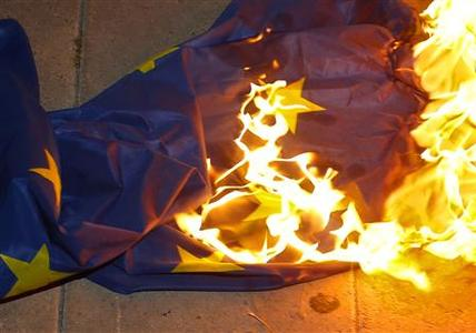 An European Union flag is seen ablaze during an anti-bailout rally outside the presidential palace in Nicosia March 27, 2013. REUTERS-Yannis Behrakis