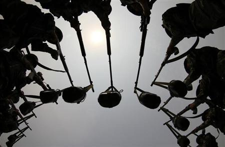 Paramilitary soldiers hold guns with water bottles hanging from their ends during aiming training in Zhengzhou, Henan province July 11, 2011. REUTERS/China Daily