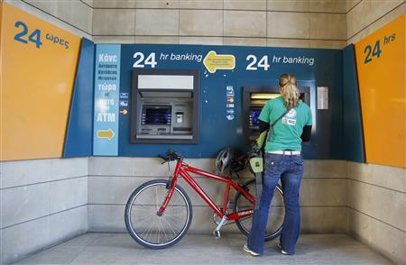 A woman withdraws money from an ATM outside a Bank of Cyprus branch before it opens in Nicosia March 28, 2013. REUTERS/Bogdan Cristel