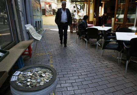 A tourist walks by a pan full of pre-Euro Cypriot coins in Nicosia old town March 23, 2013. REUTERS/Yannis Behrakis