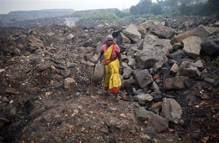 A local woman prepares to collect coal from an open cast coal field at Dhanbad district in Jharkhand September 20, 2012. REUTERS/Ahmad Masood/Files
