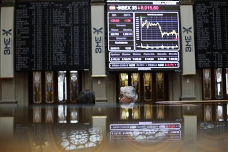 Traders talk next to an electronic board at Madrid's Bourse March 26, 2013. REUTERS/Susana Vera