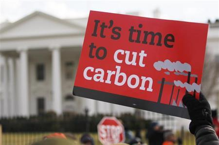 A demonstrator holds up a sign during a march past the White House to protest against the Keystone XL pipeline in Washington, February 17, 2013. REUTERS/Richard Clement