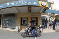Devant une succursale de Bank of Cyprus à Nicosie. Les banques chypriotes ont rouvert jeudi dans des conditions très strictes après douze jours de fermeture, mais la ruée redoutée vers les guichets après l'adoption d'un plan de sauvetage draconien ne s'est pas produite. /Photo prise le 28 mars 2013/REUTERS/Bogdan Cristel