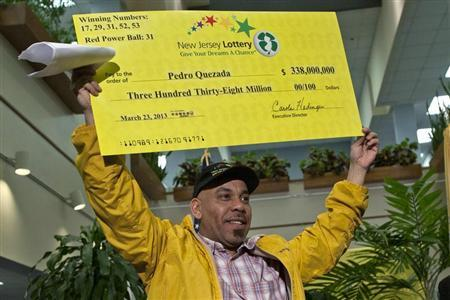 Pedro Quezada holds up the promotional Powerball jackpot check of $338 million at the end of a news conference at the New Jersey Lottery headquarters in Trenton, March 26, 2013. REUTERS/Eduardo Munoz