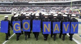 Midshipmen from the United States Naval Academy display placards on their backs as the exit field before the start of the Army versus Navy NCAA football game in Philadelphia, Pennsylvania, December 8, 2012. REUTERS/Tim Shaffer