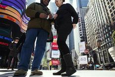 A woman buys individual cigarettes in Times Square during a warm winter day in New York March 6, 2012. REUTERS/Lucas Jackson