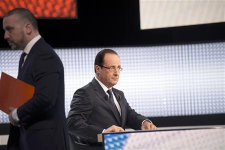 France's President Francois Hollande sits with his notes before appearing on France 2 television prime time news broadcast for an interview at their studios in Paris, March 28, 2013. REUTERS/Fred Dufour/Pool