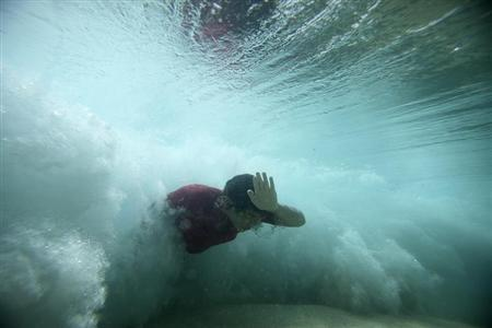 A bodysurfer punches through a wave at the Ehukai sandbar near the surf break known as 'Pipeline' on the North Shore of Oahu, Hawaii March 20, 2013. REUTERS/Hugh Gentry