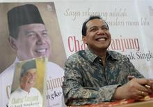 Founder and chairman CT Corp Chairul Tanjung smiles as his sits in front of his portrait at a book shop during his book launch in Jakarta July 2, 2012. REUTERS/Beawiharta