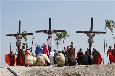 Ruben Enaje (C), 52, who is portraying Jesus Christ for the 27th time, hangs on a cross beside two men, who portray Dismas and Gestas, after he was nailed to it during a Good Friday crucifixion re-enactment in San Pedro Cutud town, Pampanga province, north of Manila March 29, 2013. REUTERS/Romeo Ranoco