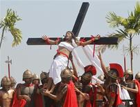 Ruben Enaje, 52, who is portraying Jesus Christ for the 27th time, is raised on a wooden cross by a group of men playing Roman soldiers after he was nailed to it during a Good Friday crucifixion re-enactment in San Pedro Cutud town, Pampanga province, north of Manila March 29, 2013. The Roman Catholic church frowns upon the gory spectacle held in the Philippine village of Cutud every Good Friday but does nothing to deter the faithful from emulating the suffering of Christ and taking a painful route to penitence. Holy Week is celebrated in many Christian traditions during the week before Easter. REUTERS/Romeo Ranoco