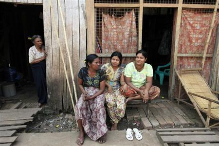 Muslim women sit in front of their home in Letpadan March 29, 2013. Since 42 people were killed in violence that erupted in Meikhtila town on March 20, unrest led by hardline Buddhists has spread to at least 10 other towns and villages in central Myanmar, with the latest incidents only a two-hour drive from Yangon. Further south, police in Letpadan have stepped up patrols in the farming village of 22,000 people about 160 km (100 miles) from Yangon. REUTERS/Soe Zeya Tun