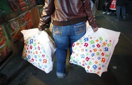 A customer walks away with bags of goods outside the Toys R Us store in Times Square on the Thanksgiving Day holiday in New York, November 22, 2012. REUTERS/Carlo Allegri