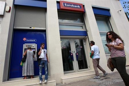 A woman (L) makes a transaction at an ATM machine outside a Eurobank branch in central Athens October 5, 2012. REUTERS/John Kolesidis