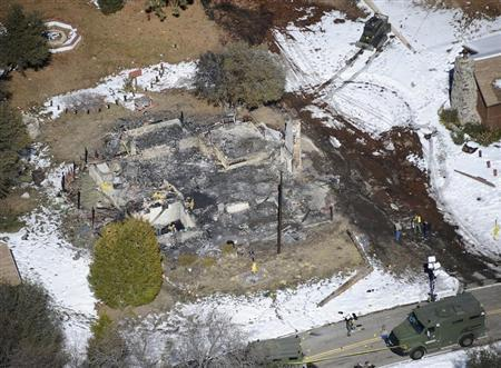 Authorities stand at the site of a burnt out cabin near Angelus Oaks, California February 13, 2013, where police believe they engaged in a shootout with fugitive former Los Angeles police officer Christopher Dorner. REUTERS/Gene Blevins