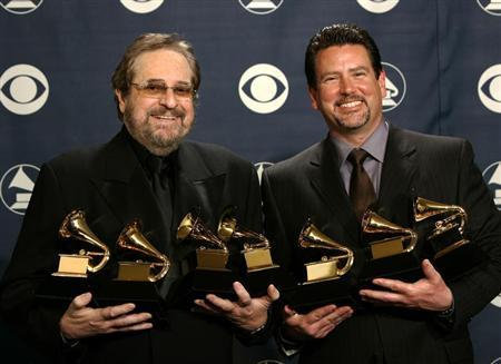 Producers Phil Ramone and John Burk hold the awards won by Ray Charles and his album ''Genius Loves Company'' at the 47th annual Grammy Awards in Los Angeles. REUTERS/Mike Blake