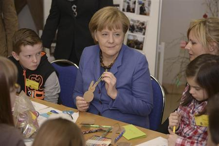 German Chancellor Angela Merkel makes handicrafts during her visit to a several generations house (Mehrgenerationenhaus) ''Dorflinde'' in Langenfeld in Bavaria, March 25, 2013. REUTERS/Daniel Peter/Pool