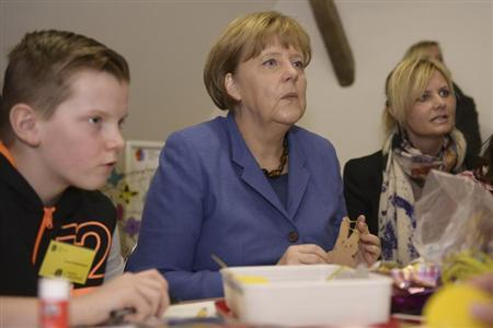 German Chancellor Angela Merkel handicrafts during her visit to a several generations house (Mehrgenerationenhaus) ''Dorflinde'' in Langenfeld in Bavaria, March 25, 2013. REUTERS/Daniel Peter/Pool