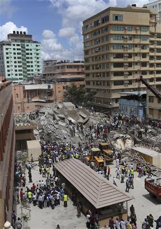 An aerial view shows bystanders watching rescuers search for survivors amongst the rubble of a collapsed building in the Kariakoo district of central Dar es Salaam March 29, 2013. REUTERS/Emmanuel Herman