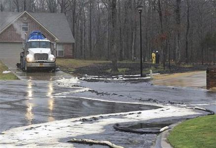 Men wearing protective clothing survey cleanup efforts March 30, 2013 where an underground crude oil pipeline ruptured in the Northwood subdivision in Mayflower, Arkansas. REUTERS-Rick McFarland-Arkansas Democrat-Gazette-Handout